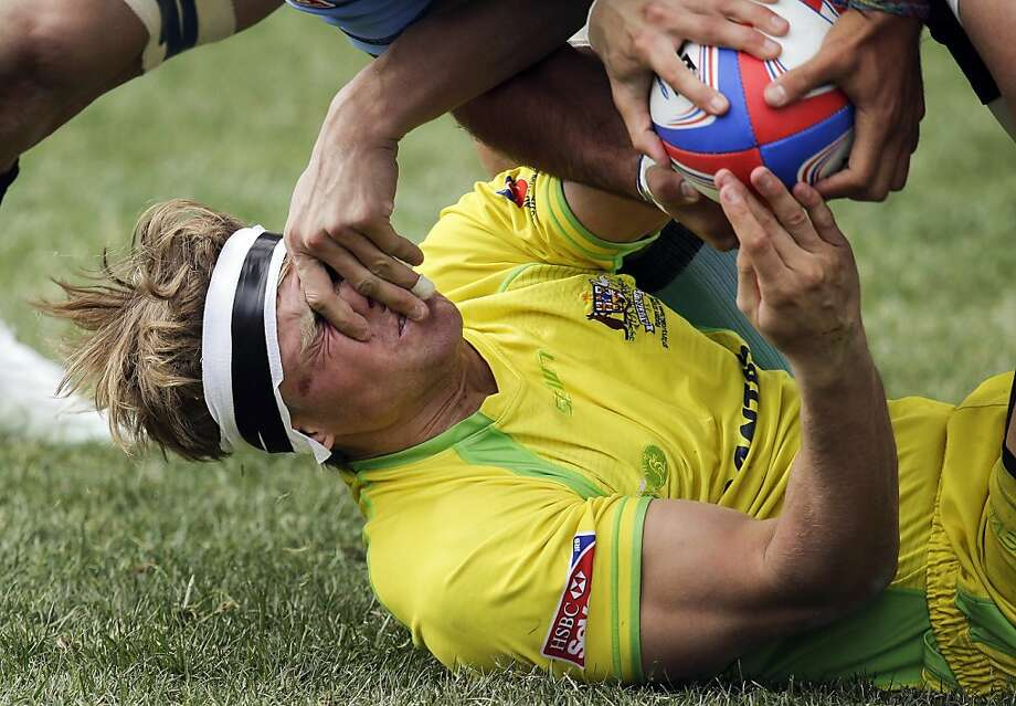 Australia's Lewis Holland tries to hand the ball off to a teammate as his face is grabbed by a Uruguayan player during the Shield Final of the Sevens Rugby World Series tournament, Sunday, Feb. 10, 2013, in Las Vegas. Australia won 41-0. (AP Photo/Julie Jacobson) Photo: Julie Jacobson, Associated Press