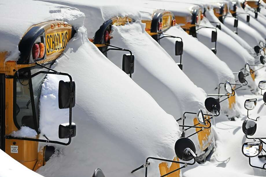 A mantle of new-fallen snow covers school buses in Hartford, Conn. Photo: Jessica Hill, Associated Press