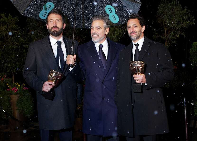 (L-R) US actor and directors Ben Affleck and George Clooney and US actor Grant Heslov hold their awa