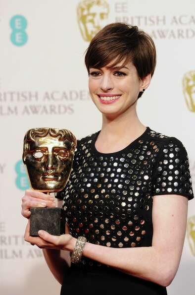 Actress Anne Hathaway, winner of the Supporting Actress award, poses in the press room at the EE Bri