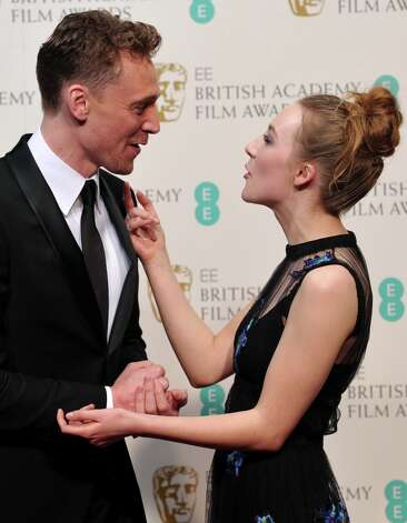 Presenters Tom Hiddlestone (L) and Saoirse Ronan pose in the Press Room during the annual BAFTA British Academy Film Awards at the Royal Opera House in London on February 10, 2013.  AFP PHOTO/Carl COURT Photo: CARL COURT, AFP/Getty Images / AFP