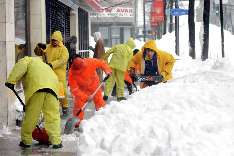 A crew working for property manager Justin Goldberg, clears the sidewalk at 1023 Main St. in Brid