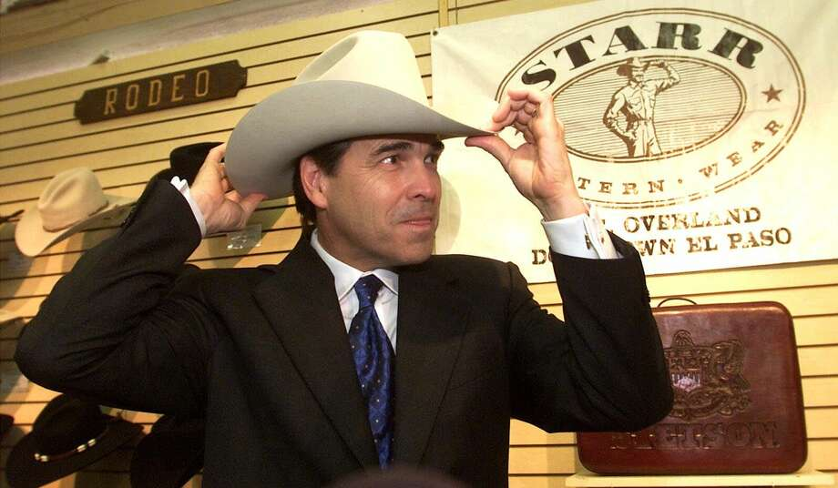 Texas Gov. Rick Perry adjusts a new cowboy hat that was given to him by Starr Western Wear owner Enoch Kimmelman on Thursday, Aug. 2, 2001, in El Paso. Photo: RUBEN R. RAMIREZ, AP / EL PASO TIMES