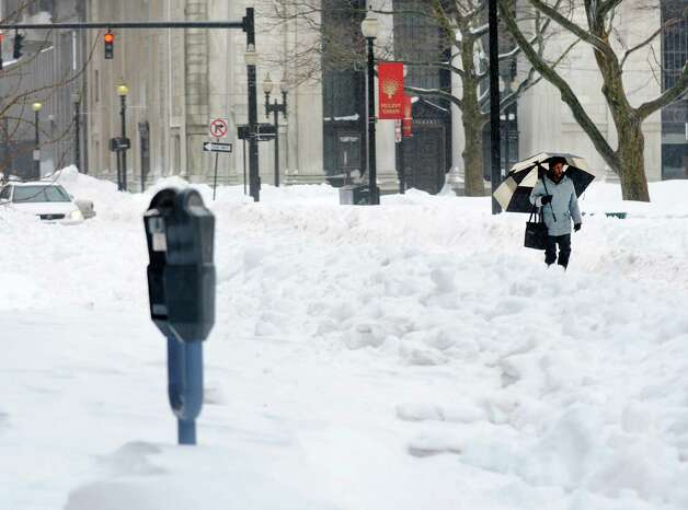 Pedestrians continue to struggle to get around the city as they walk around vehicles and snowbanks on Main St. in Bridgeport, Conn. on Monday Feb. 11, 2013. Photo: Cathy Zuraw / Connecticut Post