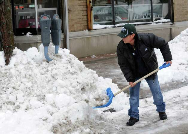 Zenon Hernandez clears the sidewalk in front of Junior's Jewelry which was open for business in Bridgeport, Conn. on Monday Feb. 11, 2013. Photo: Cathy Zuraw / Connecticut Post