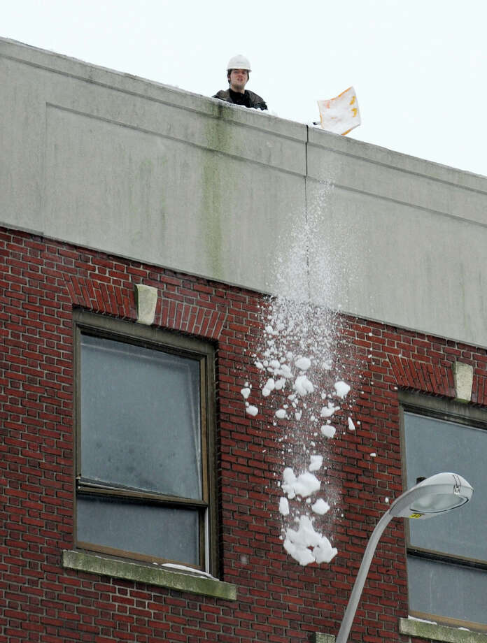 A worker shovels off the roof on the back side of the former Mechanics & Farmers building at the corner of Bank St. and Middle St. in Bridgeport, Conn. on Monday Feb. 11, 2013. Photo: Cathy Zuraw / Connecticut Post