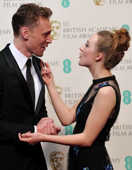 Presenters Tom Hiddlestone (L) and Saoirse Ronan pose in the Press Room during the annual BAFTA Brit