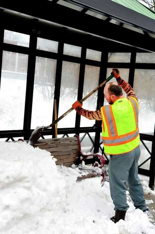 Pat Hanrahan of the Danbury Forestry Department clears a snow-packed bus stop bench on Main Street in Danbury Monday, Feb. 11, 2012. Photo: Michael Duffy / The News-Times
