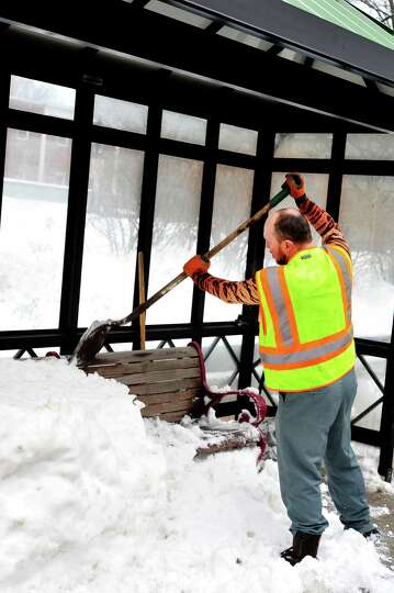 Pat Hanrahan of the Danbury Forestry Department clears a snow-packed bus stop bench on Main Street i