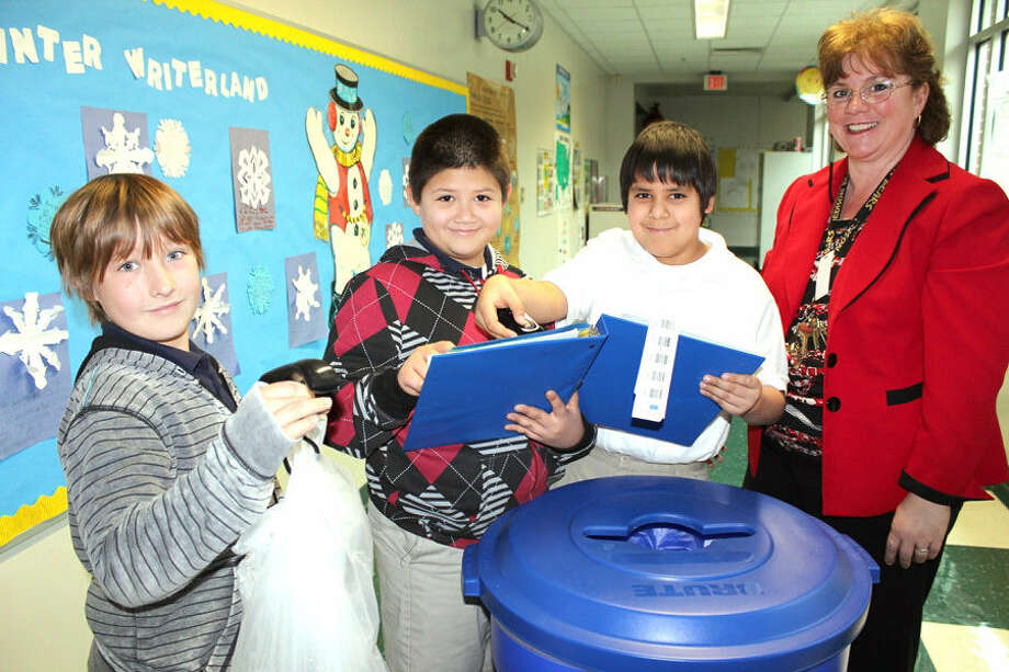 Beacon Hill Elementary principal Trace Mahbubani, right, oversees fourth-graders Simon Whitus, left, weighing materials, while Silas Prado records data, and Dimitrius Idrogo scans barcodes to record the amount of pounds recycled. Photo: Courtesy Photo