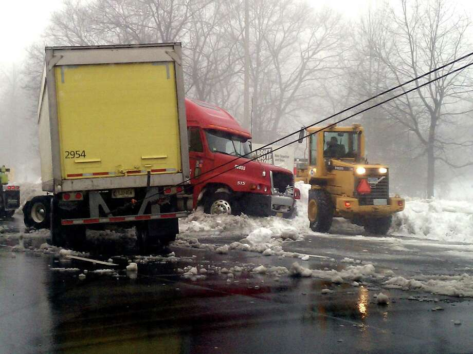 A tractor-trailer was traveling southbound on Interstate 95 between exits 35 and 34 in Milford, Conn. shortly before 3 p.m. when slippery conditions caused it to jackknife on the roadway, police said. The accident closed the right and center lanes for more than an hour. State Police said there were no injuries. Photo: Ted Tompkins / Connecticut Post