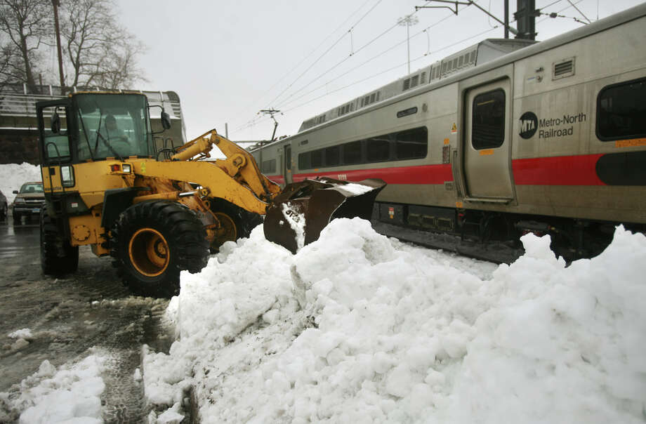 A loader clears snow near a Metro North commuter train at the Union Station railyards in New Haven, Conn. on Monday, February 11, 2013. Photo: Brian A. Pounds / Connecticut Post