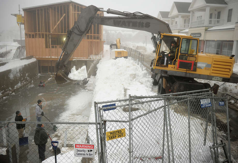 Manny Rodrigues, owner of Manny's Excavating, uses an excavator to remove snow from the foundation of the Colony Grill construction site on Broad Street in downtown Milford, Conn. on Monday, February 11, 2013. Photo: Brian A. Pounds / Connecticut Post