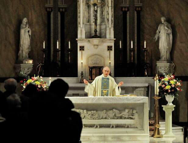 The Rev. Gregg Mecca celebrates Mass at St. Peter's Church in Danbury Monday, Feb. 11, 2012. He asked the congregation to pray for the pope's health. Photo: Michael Duffy / The News-Times