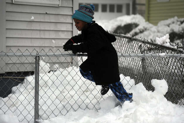 A young girl plays in the snow on Hewitt St., in Bridgeport, Conn., Feb. 11th, 2013. Photo: Ned Gerard / Connecticut Post