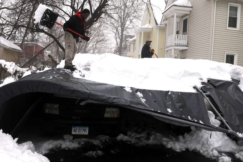 A family works to remove snow from a collapsed car shelter behind a home on Hewitt St., in Bridgepor