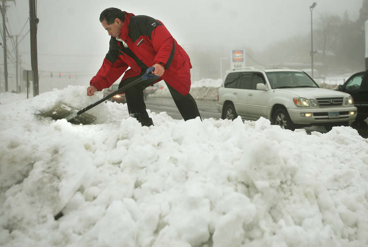 Hector Marroquin shovels down the height of snowbanks outside a business on the Post Road in Milford, Conn. on Monday, February 11, 2013. Marroquin was concerned that exiting customers wouldn't be able to see the oncoming traffic.