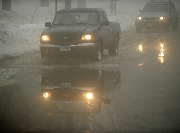 Vehicles cross a flooded section of North Street in Milford, Conn. caused by rain and melting snow on Monday, February 11, 2013. Photo: Brian A. Pounds / Connecticut Post