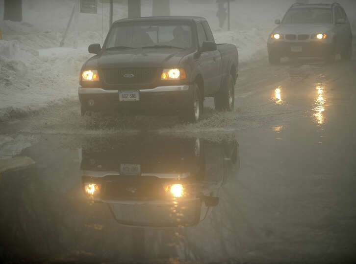 Vehicles cross a flooded section of North Street in Milford, Conn. caused by rain and melting sno