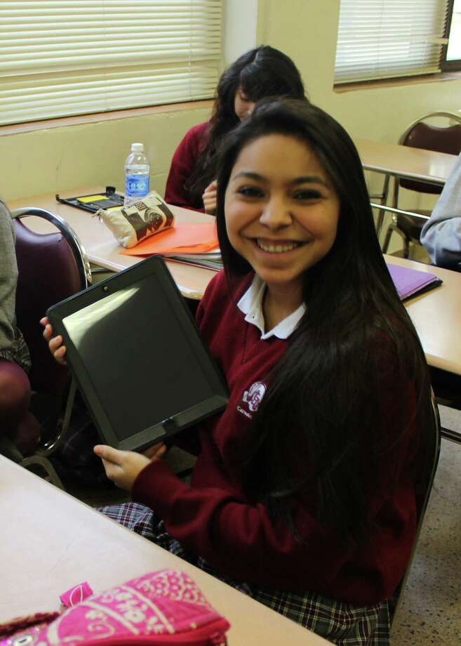 St. Anthony High School sophomore Victoria Cruz shows off her new iPad during an introduction of iPads for faculty and student use in the classroom at the Monte Vista campus. Photo: Courtesy Photo