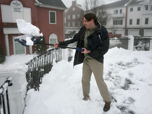 A man removes snow from the deck of the Indigo By The Water restaurant on Factory Lane in Milford, Conn. on Monday, February 11, 2013. Photo: Brian A. Pounds / Connecticut Post