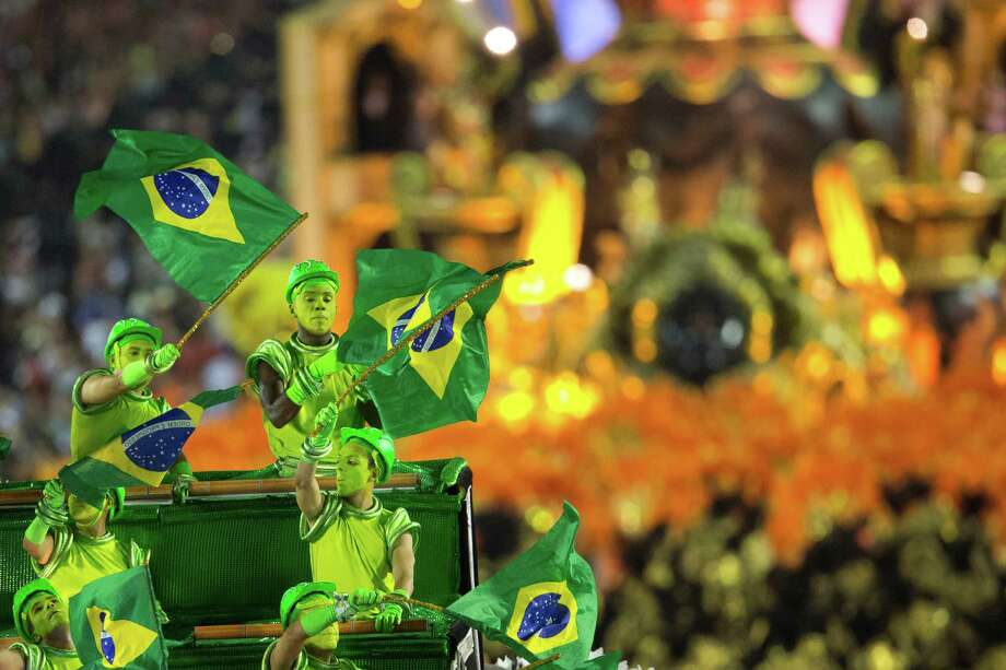 Performers from the Uniao da Ilha do Governador school wave Brazilian flags atop a float during carnival celebrations at the Sambadrome in Rio de Janeiro, Brazil, early Monday, Feb. 11, 2013. Photo: AP