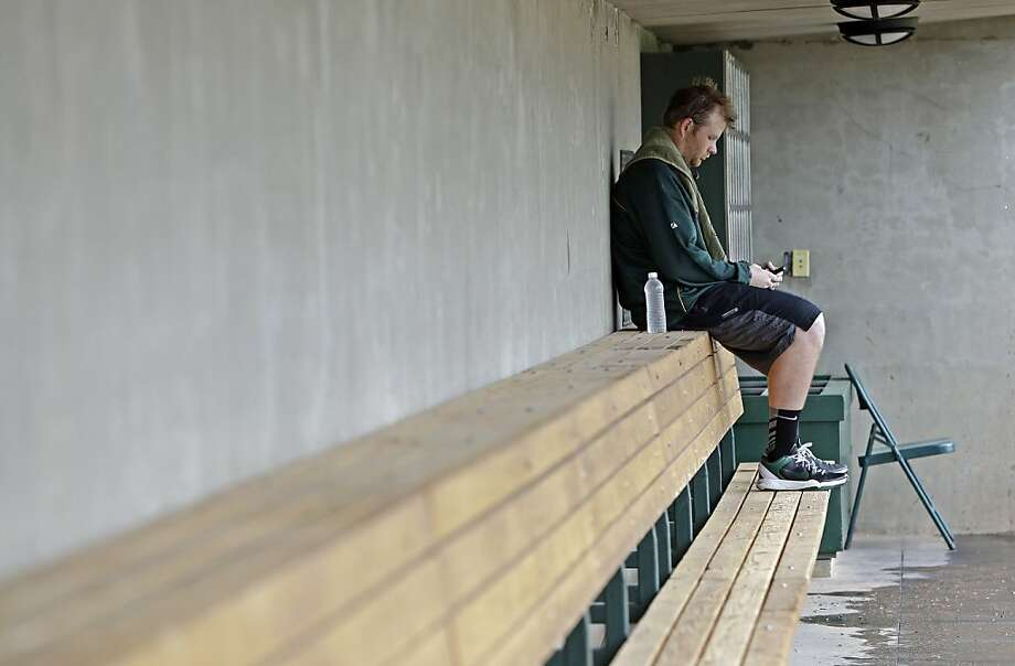 A's lefty Brett Anderson checks phone messages after reporting to spring training. Photo: Darron Cummings, Associated Press