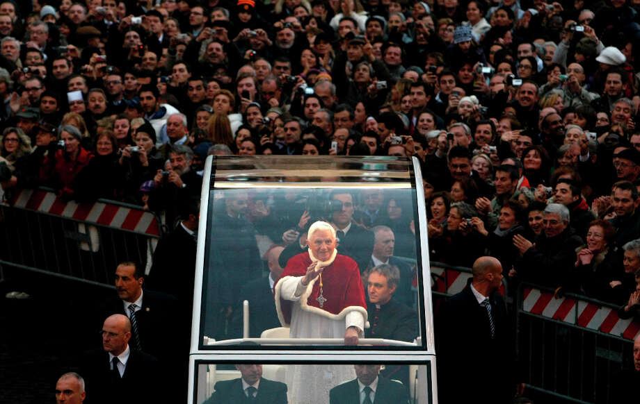FILE - In this Tuesday, Dec. 8, 2009 file photo, Pope Benedict XVI, standing at center, waves from his popemobile on his way to the Spanish Steps in central Rome, for the traditional prayer before a statue of the Virgin Mary on the occasion of the Immaculate Conception. Benedict announced Monday Feb. 11, 2013 he would  resign Feb. 28, the first pontiff to do so in nearly 600 years. The decision sets the stage for a conclave to elect a new pope before the end of March. (AP Photo/Andrew Medichini. File) Photo: ANDREW MEDICHINI, Associated Press / AP