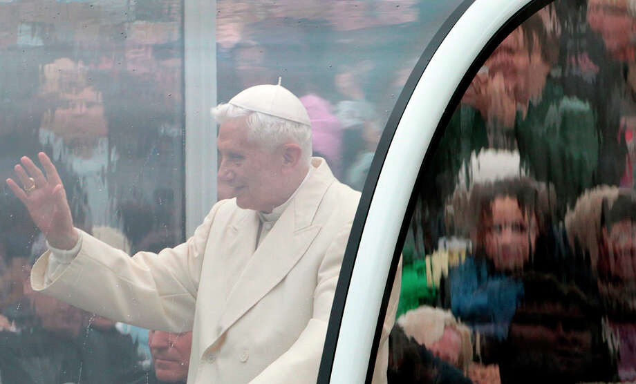 FILE - In this Wednesday, Oct. 31, 2012 file photo, Pope Benedict XVI is seen behind a window of his pope-mobile as he delivers his blessing to faithful gathered in St. Peter's Square for his general audience, at the Vatican. Benedict always cast himself as the reluctant pope, a shy bookworm who preferred solitary walks in the Alps to the public glare and the majesty of Vatican pageantry. But once in office, he never shied from charting the Catholic Church on the course he thought it needed _ a determination reflected in his stunning announcement Monday that he would be the first pope to resign since 1415. (AP Photo/Gregorio Borgia) Photo: Gregorio Borgia, Associated Press / AP