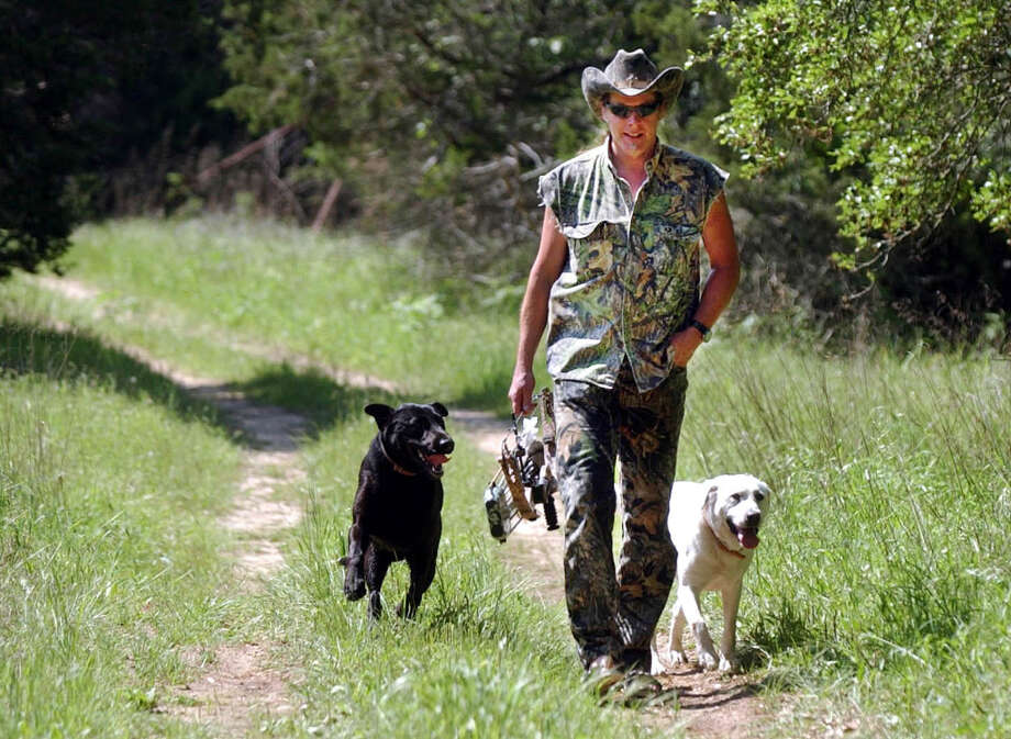 ** ADVANCE FOR MONDAY, MAY 16 ** Ted Nugent walks with his dogs on his ranch near Crawford, Texas, Friday, April 22, 2005.  At 56, Nugent is ever the Motor City Madman - the hyper rock star, avid hunter and outspoken National Rifle Association board member. But the newly relocated Texan can't help but be amused by his newfound acceptance among more and more Americans. (AP Photo/LM Otero).     HOUCHRON CAPTION (05/22/2005 - 2-star)  SECMETRO: TEXAN BY CHOICE: Ted Nugent returns to his house after bow-hunting practice on his property near Crawford. Photo: LM OTERO, AP / AP