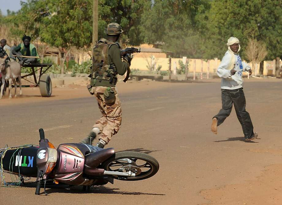 A Malian soldier moves to arrest a fleeing man at a checkpoint a day after radical Islamist militants battled French and Malian troops in a brazen reinvasion of the city of Gao. Photo: Pascal Guyot, AFP/Getty Images