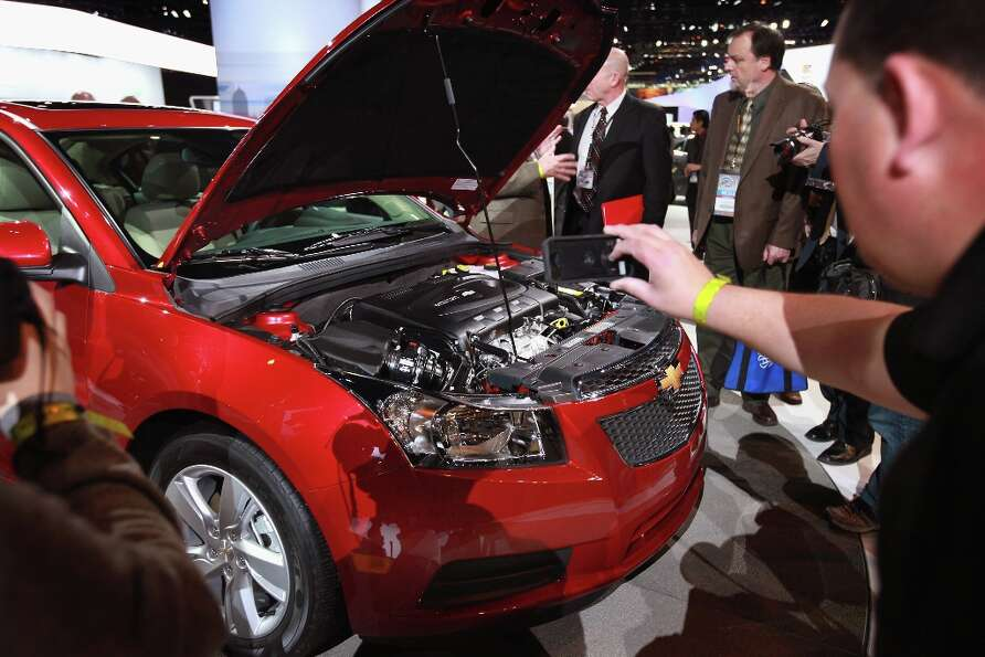 CHICAGO, IL - FEBRUARY 07:  Members of the press look at the motor in Chevrolet's 2014 Cruze with a