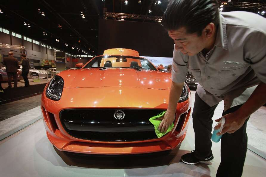 CHICAGO, IL - FEBRUARY 07: Philip Zambrano details a 2014 Jaguar F-Type S at the Chicago Auto Show o