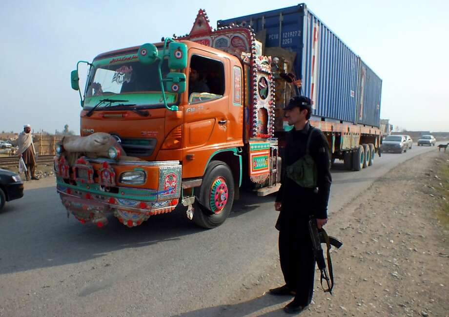A Pakistani tribal policeman stands guard along a road used by NATO trucks as they reportedly bring supplies from neighboring Afghanistan in Jamrud, in the tribal area of Khyber, Pakistan, on Monday, Feb. 11, 2013. The U.S. says it has started using the land route through Pakistan to pull American military equipment out of Afghanistan. (AP Photo/Jibran Yousufzai) Photo: Jibran Yousufzai, Associated Press
