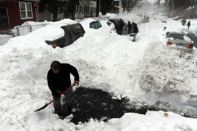 Neighbors works to clear snow from Carroll Ave., in Bridgeport, Conn., Feb. 11th, 2013. Photo: Ned Gerard / Connecticut Post