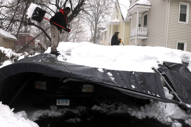A family works to remove snow from a collapsed car shelter behind a home on Hewitt St., in Bridgeport, Conn., Feb. 11th, 2013. Photo: Ned Gerard / Connecticut Post