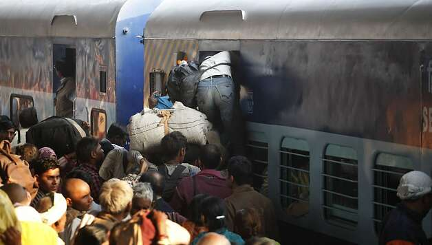 Hindu devotees returning from Maha Kumbh jostle to get in a coach of a train at the main railway station of Allahabad, India, Monday, Feb. 11, 2013. Dozens of people were killed after Sunday's stampede in a train station in Allahabad where millions of devotees had gathered for a Hindu festival that is one of the world's largest religious gatherings. (AP Photo/ Rajesh Kumar Singh) Photo: Rajesh Kumar Singh, Associated Press