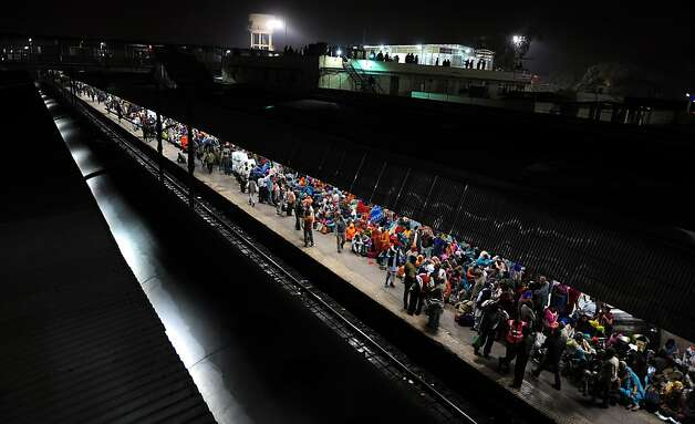 Indian Hindu devotees wait to board a train, at the site of a stampede the night before, at the main station in Allahabad  on February 11, 2013. Survivors of a stampede that killed 36 people at India's Kumbh Mela blamed the tragedy Monday on baton-charging police and the slow response of medics as the massive festival's chief organiser resigned.  AFP PHOTO/ SANJAY KANOJIASanjay Kanojia/AFP/Getty Images Photo: Sanjay Kanojia, AFP/Getty Images