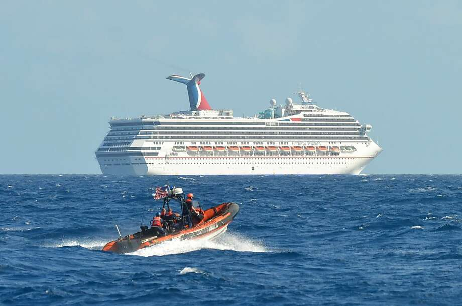 In this image released by the U.S. Coast Guard on Feb. 11, 2013, a small boat belonging to the Coast Guard Cutter Vigorous patrols near the cruise ship Carnival Triumph in the Gulf of Mexico, Feb. 11, 2013. The Carnival Triumph has been floating aimlessly about 150 miles off the Yucatan Peninsula since a fire erupted in the aft engine room early Sunday, knocking out the ship's propulsion system. No one was injured and the fire was extinguished. (AP Photo/U.S. Coast Guard- Lt. Cmdr. Paul McConnell) Photo: Lt. Cmdr. Paul McConnell, Associated Press