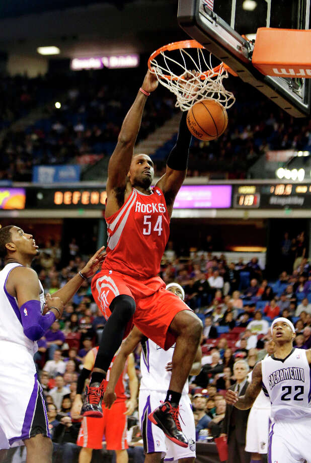 Rockets forward Patrick Patterson dunks over Kings forward Jason Thompson. Photo: Rich Pedroncelli