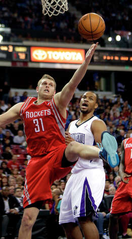 Rockets center Cole Aldrich grabs a rebound over Chuck Hayes of the Kings. Photo: Rich Pedroncelli