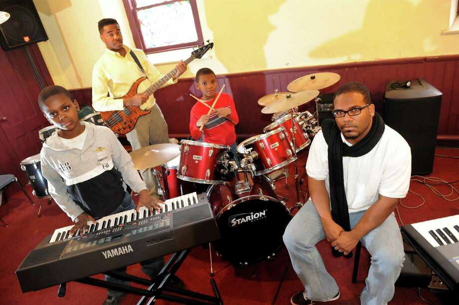 Pastor E'van Majors joins some of his band members on Thursday, Feb. 7, 2013, at Power House City of Deliverance in Albany, N.Y. From left are Michai Oliver, 11, Malcolm Harrison, 20, and Josiah Majors, 7, E'van's son. The church struggles to rebuild their music program after thieves stole their quality sound system and instruments. (Cindy Schultz / Times Union) Photo: Cindy Schultz / 10021067A