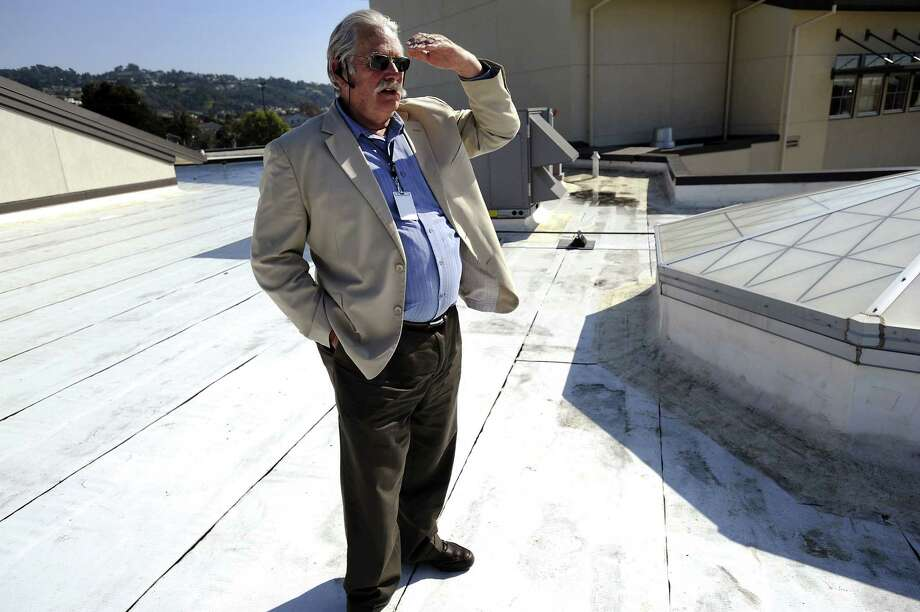"Facilities project manager Andrew Mixer explains the energy efficient ""cool roofing"" on top of a library at a school in Richmond, Calif.  ""Cool roofs and pavement"" are specifically made white roofs and pavement that reflect back more light and heat. Photo: Special To The Chronicle"