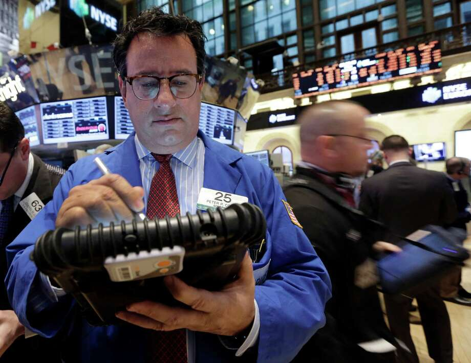 FILE - In this Feb. 8, 2013 file photo. Trader Peter Costa, left, works on the floor of the New York Stock Exchange, in New York. Stock markets in Hong Kong, mainland China and Seoul were among those closed Monday, Feb. 11, 2013, for the Lunar New Year holiday. Japanese markets were also shut for a public holiday. European stocks were mostly higher in early trading, while Wall Street futures signaled gains ahead of the opening bell. (AP Photo/Richard Drew, File) Photo: Richard Drew