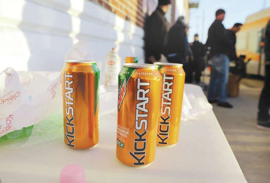 Product cans are on display during the filming of a commercial for a new PepsiCo product called Kickstart, a carbonated drink that is part juice with Mountain Dew flavor, on the streets of downtown Los Angeles Tuesday, Jan. 29, 2013.  PepsiCo Inc. is set to roll out the new drink called Kickstart this month that has Mountain Dew flavor but is made with 5 percent juice and an extra jolt of caffeine and Vitamins B and C. The company is hoping to grow sales by reaching Mountain Dew fans at a new time of day: morning.  (AP Photo/Reed Saxon) Photo: Reed Saxon / AP