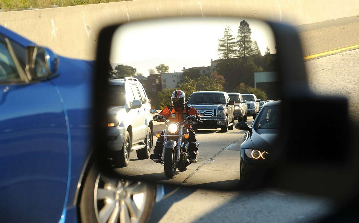 Seen reflected in a side mirror, a motorcyclist lanesplits during the evening commute on Highway 24 on Friday, Feb. 8, 2013, in Oakland, Calif.