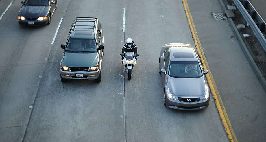A motorcyclist splits lanes during the evening commute on Highway 24 in Oakland last year. Riders say the maneuver saves time and fuel and also increases their safety. Photo: Noah Berger, Special To The Chronicle