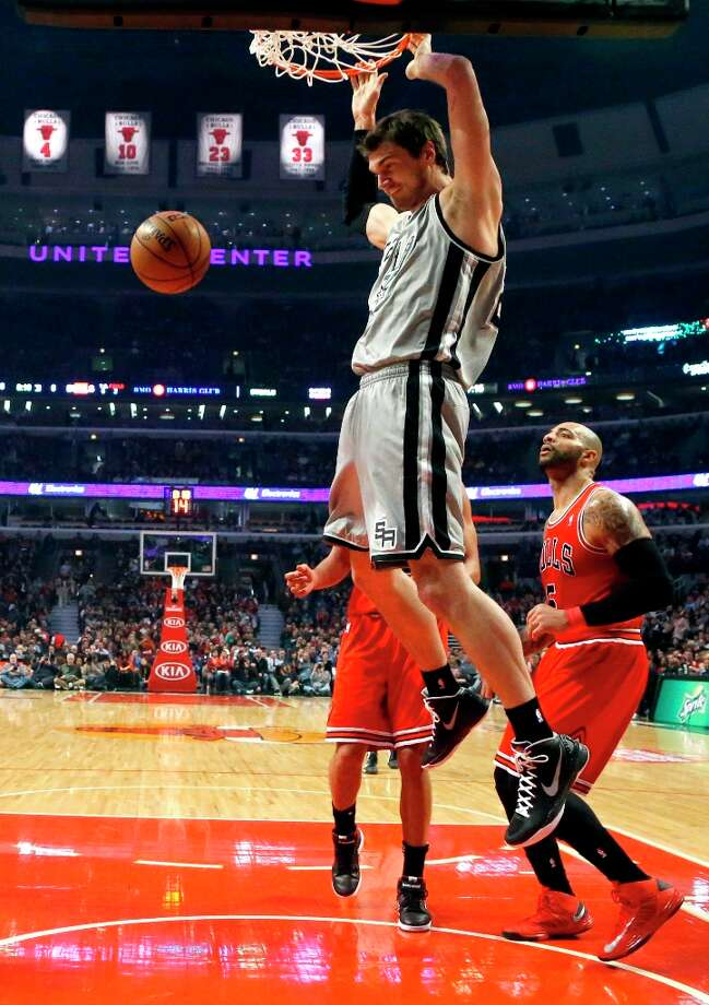 Spurs center Tiago Splitter dunks the ball past Bulls forward Carlos Boozer (5) during the first half Monday, Feb. 11, 2013, in Chicago. Photo: Charles Rex Arbogast, Associated Press / AP