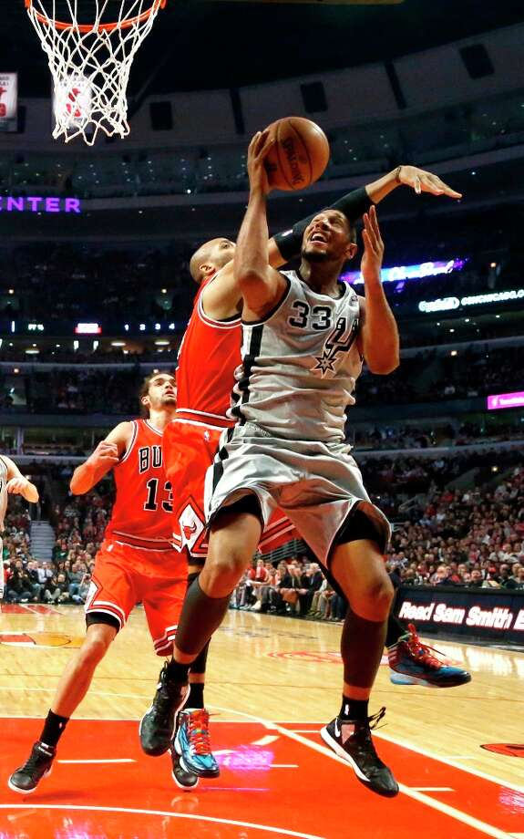 Spurs center Boris Diaw (33) shoots past Chicago Bulls forward Taj Gibson and center Joakim Noah (13) during the first half  Monday, Feb. 11, 2013, in Chicago. Photo: Charles Rex Arbogast, Associated Press / AP