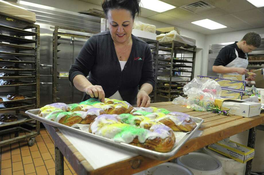 Theresa Mainella, a member of the family that owns and operates Bella Napoli Italian American Bakery, decorates Mardi Gras King Cakes on Monday, Feb. 11, 2013 in Latham, NY.  Mainella said that the bakery began making the cakes about five years ago after customers began asking for the cakes.  King cakes are decorated in purple, green and gold, which are the official colors of Mardi Gras and are served at King Cake parties in New Orleans.  Inside the cake is a small plastic baby or other token. Whoever gets the slice of cake with that piece is named king or queen for the day. That person may also be required to host the next year?s Mardi Gras party.   (Paul Buckowski / Times Union) Photo: Paul Buckowski